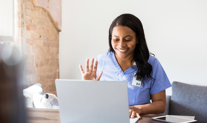 Clinician sitting in front of laptop and waving to a patient during telehealth appointment_840x500.png
