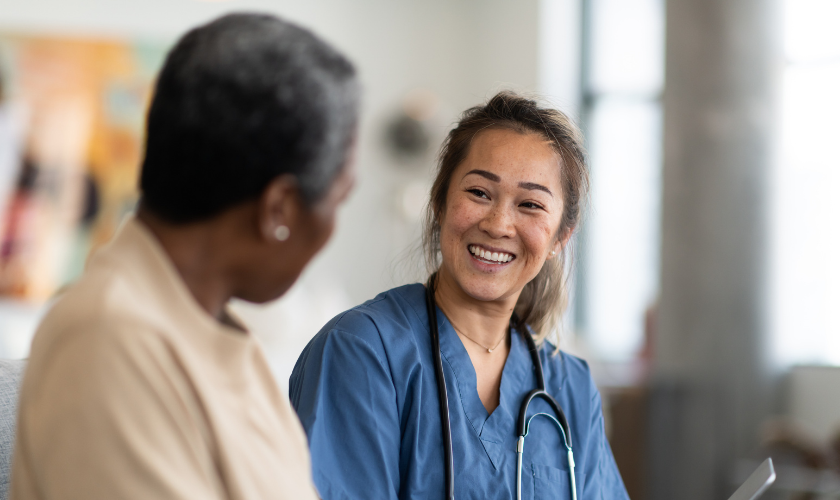 Clinician smiling and talking with a patient while holding a tablet_840x500.png