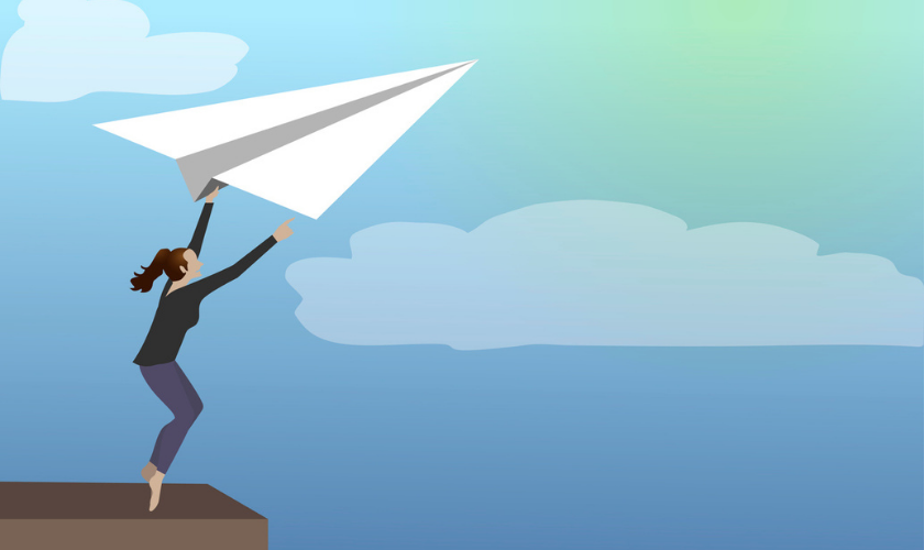 Person grabbing on to a paper airplane flying in the sky_840x500.png