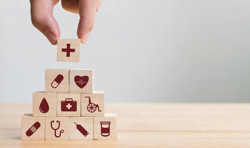 Hand Stacking Wooden Blocks on Table, Health Care Graphics Displayed on Blocks